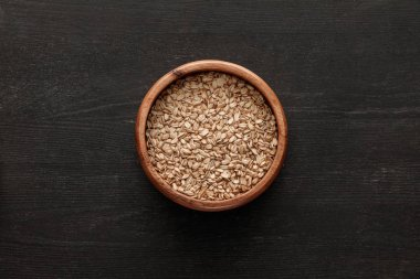 top view of brown bowl with raw oatmeal on dark wooden surface with copy space