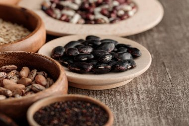 brown bowls and plates with black beans and grains on table