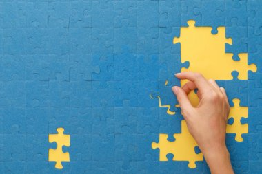 Cropped view of woman matching blue jigsaw puzzle on yellow background stock vector