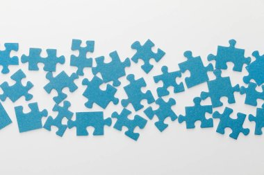 top view of scattered pieces of blue jigsaw puzzle on white background