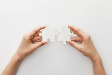 cropped view of woman holding piece of jigsaw puzzle on white background