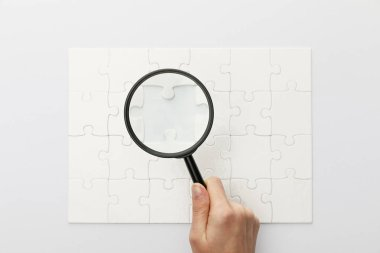 cropped view of woman holding magnifying glass under jigsaw puzzle on white background