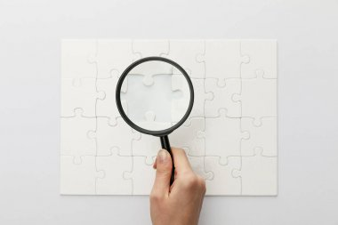 cropped view of woman holding magnifying glass under jigsaw puzzle with lost piece on white background