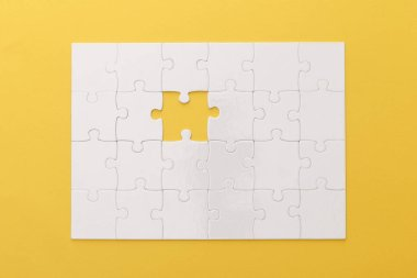 top view of white jigsaw puzzle with lost piece on yellow background