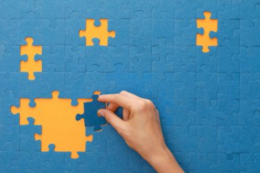 cropped view of woman putting piece of blue jigsaw puzzle on yellow background