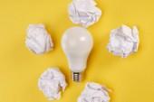 pohled na zmačkaný papír a lampu na žlutém pozadí