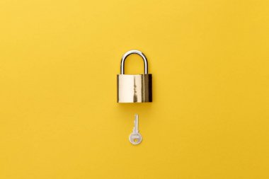 Top view of padlock and key on yellow background stock vector