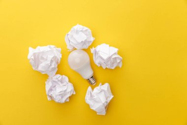 Top view of light bulb between crumpled paper on yellow background stock vector