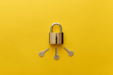 Top view of metal padlock with keys on yellow background stock vector