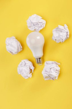 Top view of crumpled paper around light bulb on yellow background stock vector