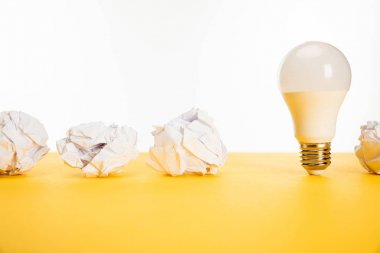 crumpled paper near light bulb on yellow surface isolated on white