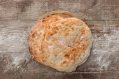 top view of round lavash bread on wooden table