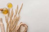 felülnézet a búza tüskékkel, sodrótűvel, olívaolajjal és liszttel a fehér felületen