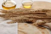 lavaš chleba pokrytý bílým ručníkem v blízkosti válcového čepu a řezací desky s hroty a olivovým olejem