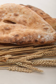 lavash bread near wheat spikes on white surface