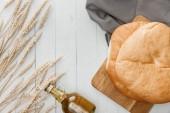 pohled na lavaši chleba na ručníku v blízkosti špiček a olivového oleje na bílém dřevěném povrchu
