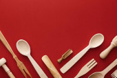 top view of woden spoons, forks, chopsticks and kitchenware on red background with copy space