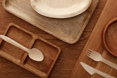pohled na dřevěné nádobí a řezací prkno s deskami a příbory na hnědém pozadí