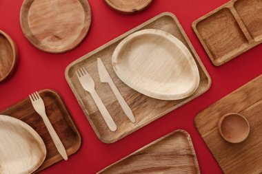 top view of eco-friendly wooden dishes, plates and cutlery on red background