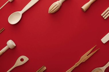 top view of natural wooden spoons, fork and kitchenware on red background with copy space
