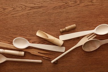 Top view of wooden cutlery and kitchenware on brown background stock vector