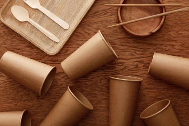 top view of wooden dishes, cutlery, chopsticks and paper cups on brown background