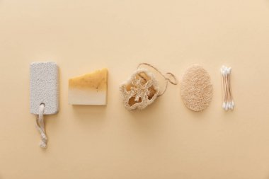 top view of natural soap near cotton swabs, loofah and pumice stone on beige background