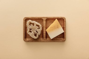 top view of brown wooden soapdish with loofah and piece of soap on beige background