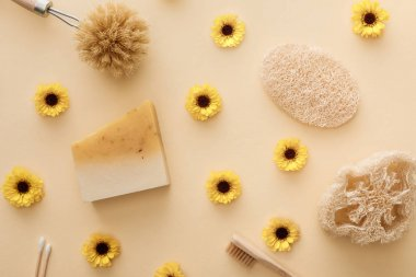 top view of loofah, cotton swabs, body brush, toothbrush and piece of soap on beige background with flowers
