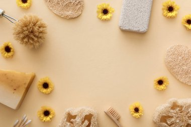top view of loofah, cotton swabs, body brush, toothbrush and piece of soap on beige background with flowers and copy space