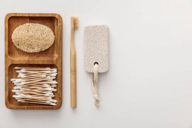 flat lay with wooden dish with cotton swabs and loofah near toothbrush and pumice stone on white background