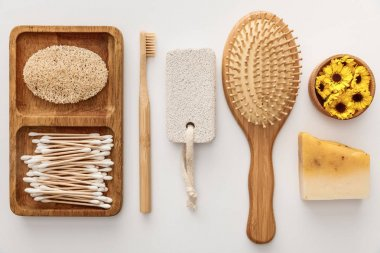 flat lay with wooden dish with cotton swabs and loofah near toothbrush, hairbrush, piece of soap, pumice stone and cup with flowers on white background