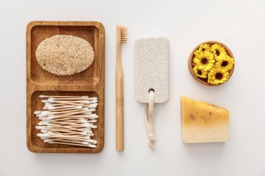 flat lay with wooden dish with cotton swabs and loofah near toothbrush, piece of soap, pumice stone and cup of flowers on white background