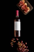 top view of rose wine bottle with blank white label near ripe grape and sliced prosciutto on baguette isolated on black