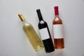 top view of bottles with white, red and rose wine on white background
