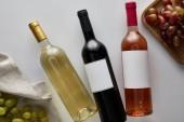 felső nézet palack fehér, vörös és rózsa bor közelében szőlő fehér háttér