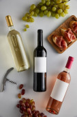 top view of bottles with white, red and rose wine near grape, corkscrew and sliced prosciutto on baguette on white background