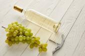 üveg fehér borral közel szőlő és dugóhúzó fehér fa felületen