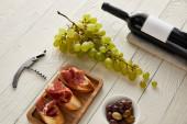 láhev s vínem u hroznů, prosciutto na bagetě, olivy a vývrtka na bílém dřevěném povrchu