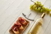 láhev s bílým vínem u hroznů, prosciutto na bagetě a vývrtka na bílém dřevěném povrchu