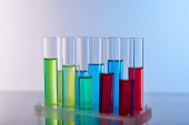 provette in vetro con liquido colorato su sfondo blu