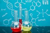 Reagenzglas und Kolben mit bunter Flüssigkeit auf blauem Hintergrund mit molekularer Struktur