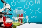 Photo microscope, glass test tubes and flasks with colorful liquid near open copybook on blue background with molecular structure