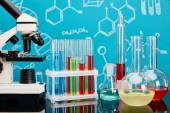 Photo microscope, glass test tubes and flasks with colorful liquid on blue background with molecular structure