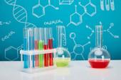 Reagenzgläser und Kolben mit bunter Flüssigkeit auf blauem Hintergrund mit molekularer Struktur