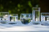 průzračná sladká voda v průhledných brýlích na dřevěném stole
