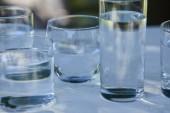průzračná sladká voda v průhledných sklenicích na dřevěném stole