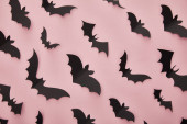 Photo top view of paper bats on pink background, Halloween decoration