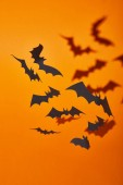 Photo paper bats with shadow on orange background, Halloween decoration