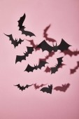 Photo black paper bats with shadow on pink background, Halloween decoration